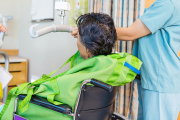 Nurse Holding Hydraulic Lift's Handle With Patient On Wheelchair