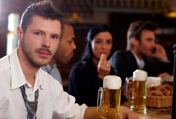 Young businessman having beer in pub