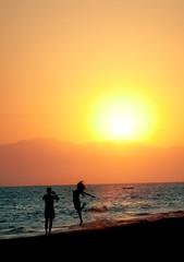 Couple having fun on beach at sunset