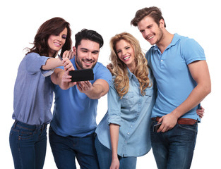 two couples of young people taking their picture with phone