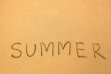Summer - text written by hand in sand on a beach.