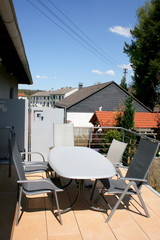 Eine Terrasse mit Edelstahlgeländer und beigen Bodenplatten
