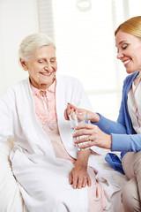 Wall Mural - Frau bietet Seniorin eine Tablette an