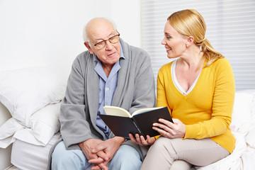 Wall Mural - Frau liest altem Mann ein Buch vor
