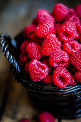 Raspberries in a basket on rustic wooden background
