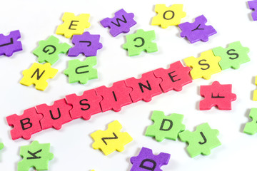 word BUSINESS formed with colorful foam puzzle  on white backgro