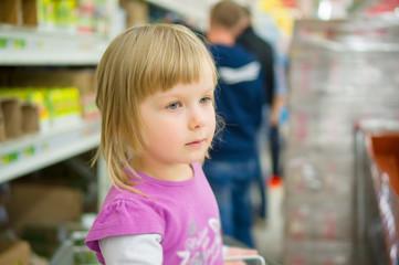 Adorable girl at shoppoing cart grimacing in supermarket