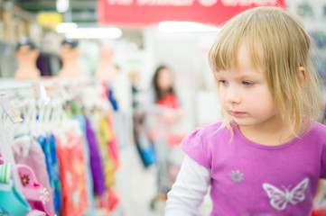 Adorable girl at shopping cart select clothes in supermarket