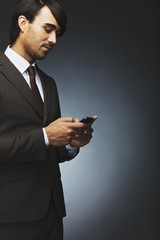 Businessman text messaging on a cell phone