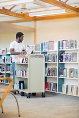 Librarian With Trolley Arranging Books In Library