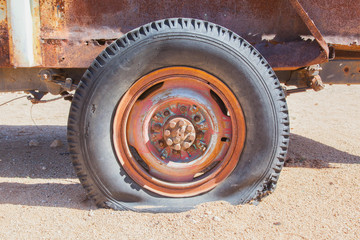 Detail of a vintage abandoned flat car tire on the side of a roa