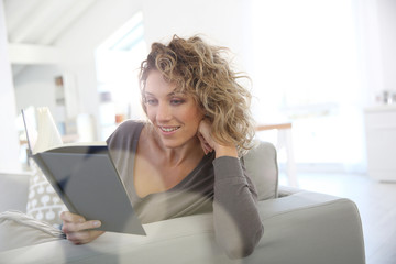Woman reading book at home in sofa
