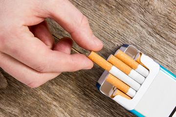 Hand takes a cigarette