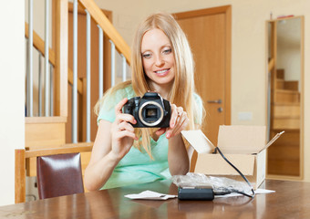 young  girl unpacking new digital camera  in home interior