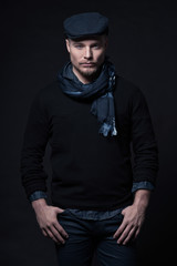 Man winter fashion. Wearing black sweater with scarf and cap. Bl