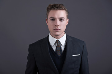 Retro fifties fashion young businessman wearing dark suit and ti