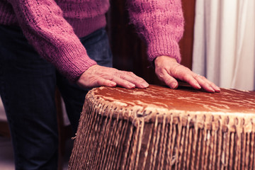 Old woman playing bongo drums
