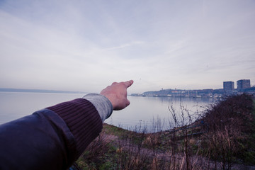 Man's hand pointing at the horizon and seaside