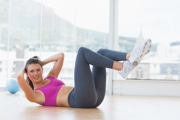 Young woman doing pilate exercises in fitness studio