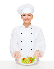 smiling female chef with salad on plate