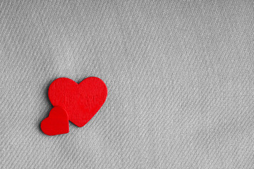 Red wooden decorative hearts on gray cloth background.