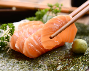 Chopsticks holding salmon sashimi slice