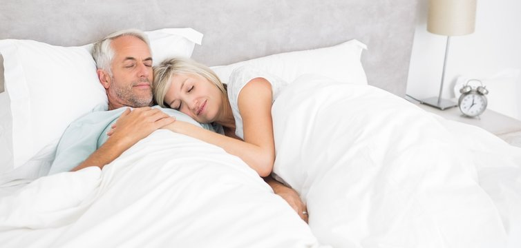 Loving mature man and woman lying in bed