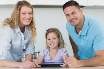 Parents and cute girl using digital tablet