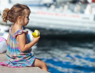 Little blond girl sits on the dock with pear in her hand.