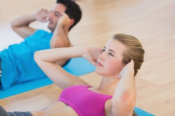 Side view of determined young couple doing sit ups