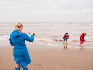 woman photographing children playing on beach with smart phone