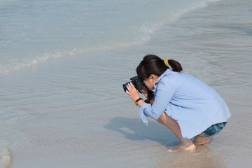woman on beach taking photo with camera