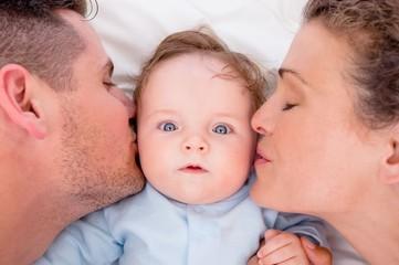 Loving parents kissing baby