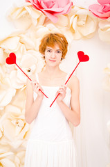 girl in white dress with red heart in hands