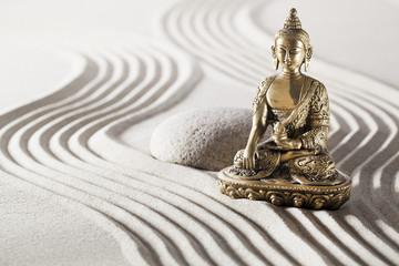 Buddha in zen garden with smooth lines in sand