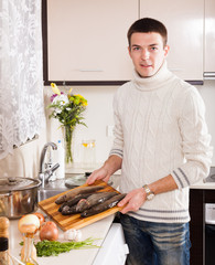 man with raw trout fish