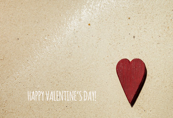 Red heart on the sandy beach.  with text happy valentines!