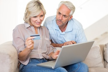 Mature couple doing online shopping at home