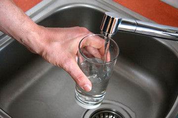 Man's hand pouring tap water to the glass