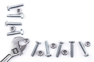 Screws, nuts and spanner on white background