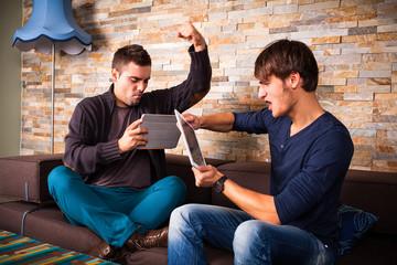 2 Männer spielen gegeneinander per Tablet