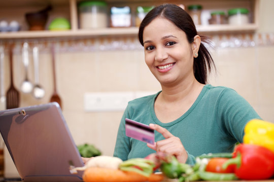 Smiling young woman online shopping