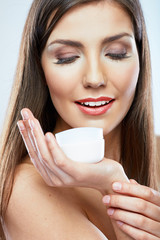 Woman hold cosmetic cream. Beautiful face young model.