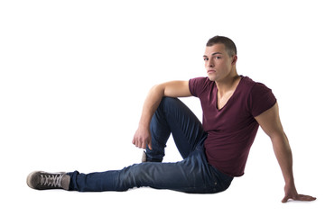 Full body shot of handsome young man sitting on floor
