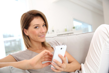 Middle-aged woman sending message with smartphone