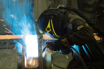 welder works with electric welding machine. metall