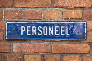 "Old sign with the Dutch text ""Personnel"" on a brick wall"