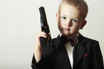 Stylish Agent.Child in Bow tie.Handsome Boy with Toy Gun