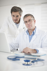 Clinical Director and his assistant discussing around a computer