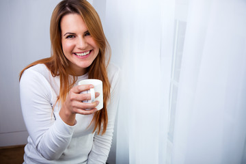 Young woman sitting by a window drinking a hot drink